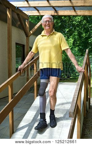 Senior Leg Amputee Walking Down Ramp For Exercise.