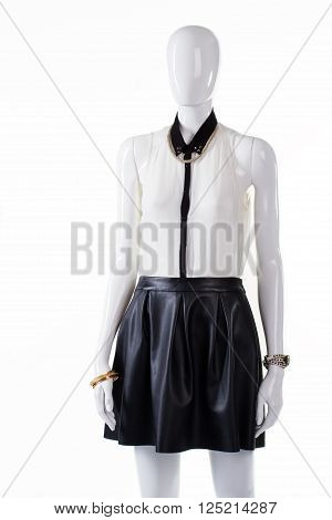 Mannequin wearing blouse and skirt. Woman's leather skirt with blouse. Blouse and skirt with folds. Luxury summer outfit on showcase.