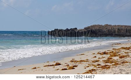 Rocky outcropping into the turquoise Indian Ocean waters at Trigg Beach with gentle waves and seaweed under a blue sky in Western Australia.