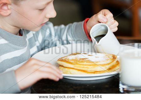 beautiful little boy pouring maple syrup at pancakes for breakfast