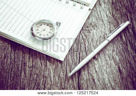 Pocket watch on notebook for notes, On old textured wood.