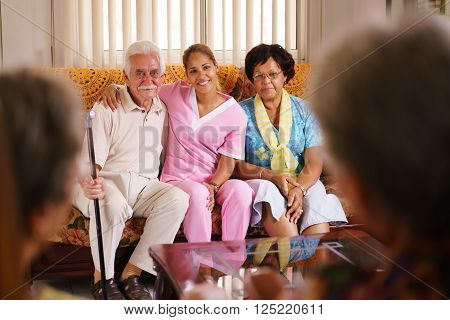 Old people in geriatric hospice: Elderly man and woman hugging a young nurse, showing a friendly relationship between personnel and patients.