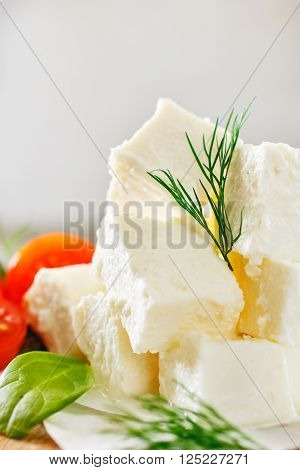 Closeup slices feta cheese with dill and cherry tomatoes