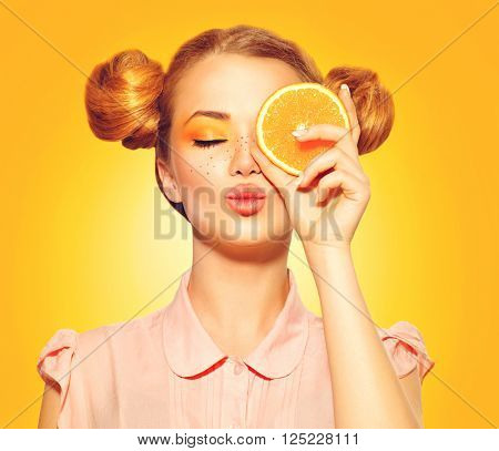 Beauty Model Girl takes Juicy Oranges. Beautiful Joyful teen girl with freckles, funny red hairstyle and yellow makeup. Professional make up. Orange Slice