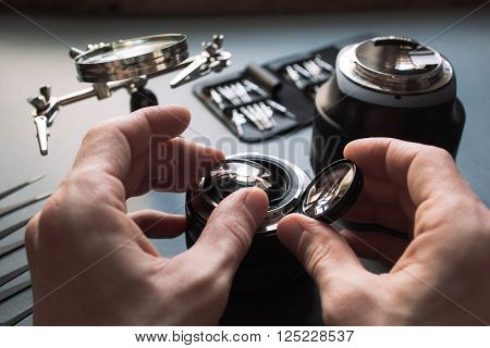 Precision prime optical dslr lens service, adjustment and alignment. Camera lens repair set in photo engineer workplace. Maintenance support of photographic 85 1.2 photo camera lens.