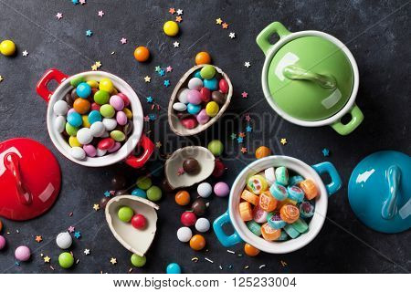 Colorful candies and lollypops on stone background. Top view