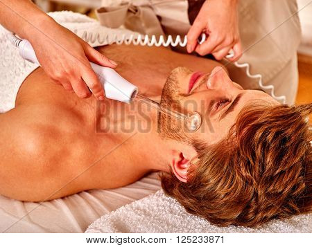 Young man receiving electric darsonval facial massage after procedure at beauty salon. Close up.