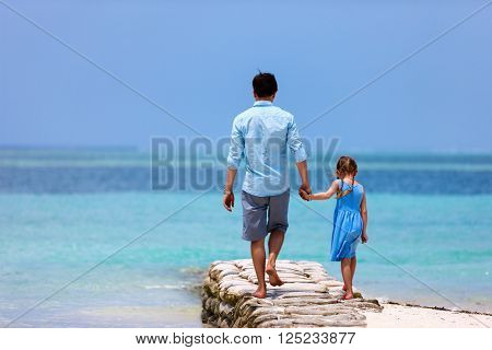 Back view of happy father and his adorable little daughter at tropical beach during summer vacation