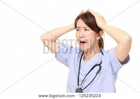 portrait of  Japanese female doctor shocked  on white background