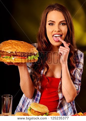 Girl eating burger with two sides. Fastfood concept.