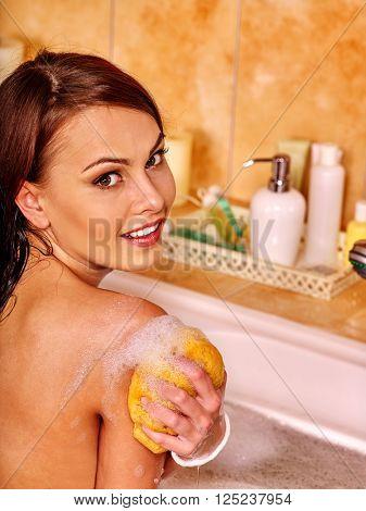 Young woman take bubble  bath. Woman washing her shoulder. She is happy.
