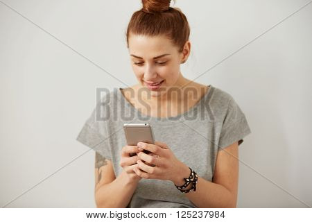 Portrait of a smiling young woman using cell phone. Beautiful happy girl chatting and texting on mobile phone on the grey background. Young woman reading a text message on smart phone