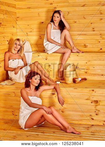 Group womens relaxing in sauna. Wooden bench.