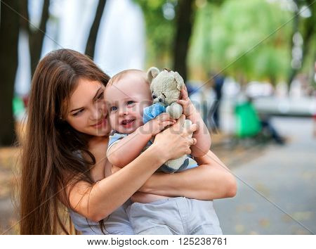 Happy mother and her baby-boy on hands play keeps teady bear toy outdoors in park. Happy young mother with her baby