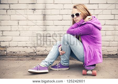 Blond Girl In Sunglasses Sits On Her Skateboard