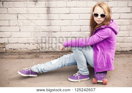 Blond Girl In Jeans And Sunglasses Sits On Skateboard