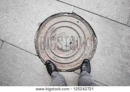 Male Feet Standing On Rusty Sewer Manhole