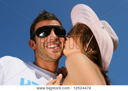 Young woman kissing his girlfriend on the cheek