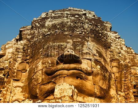 Dramatic view at sunset of one of the many large stone carved faces of Bayon Temple in Angkor Thom Angkor district Siem Reap Cambodia. Horizontal shot