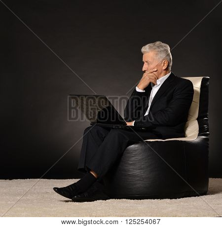 Thinking mature businessman sitting in chair on black backgroundwith a laptop