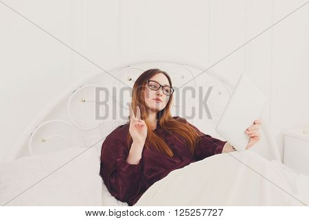 Young woman makes selfie at tablet pc in white bed. Girl in eyeglasses looks into gadget tablet pc. Morning coffee. Beautiful woman in nightwear at bed surfing internet at tablet computer. High key.