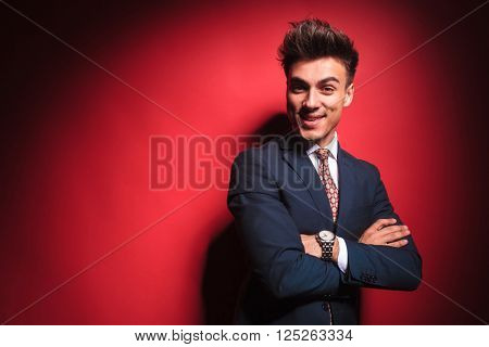 portrait of confident young businessman in black suit with red tie, posing hands crossed in red studio background while looking at the camera and smirking