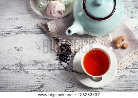 Black tea with ceramic utensils and sweets on white wooden table