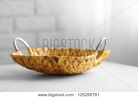 Wicker salver with metal handles on wooden table background, closeup