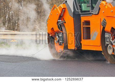 Road roller flattening new asphalt, construction of roads