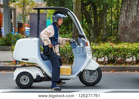 KYOTO JAPAN - NOVEMBER 22 2015: Unidentified Japanese senio worker ride a speacial design delivery motorcycle