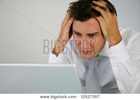 Portrait of a worried man in front of a computer