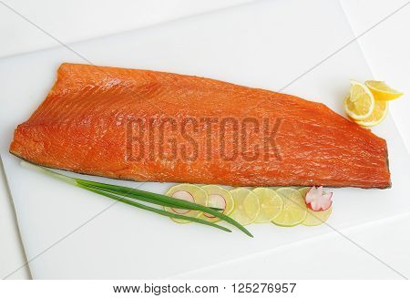 piece of smoked fish  with lemon on a white plate