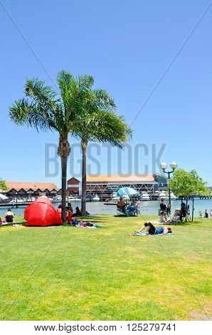 HILLARYS,WA,AUSTRALIA-JANUARY 22,2016: Families relaxing on the foreshore with swimming cove at Hillarys Boat Harbour in Hillarys, Western Australia.