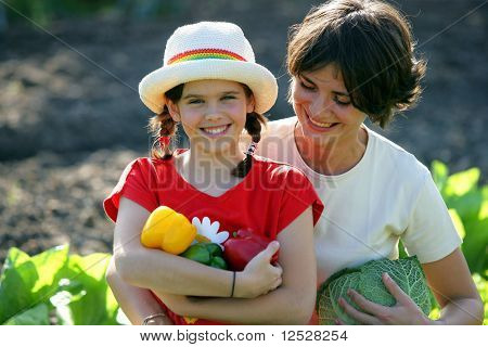 Smiling woman and little girl holding vegetables