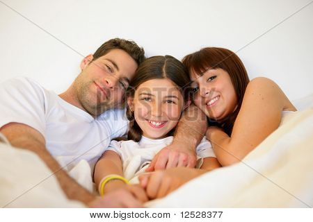 Portrait of a smiling family in a bed