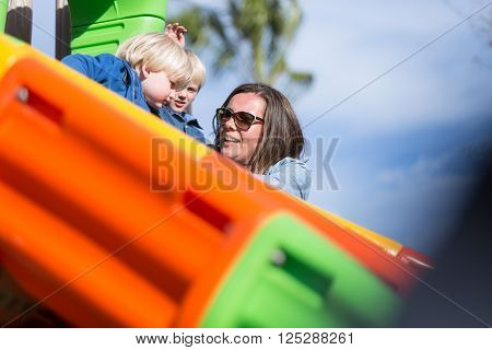 Adult woman in sunglasses with two boys on chute