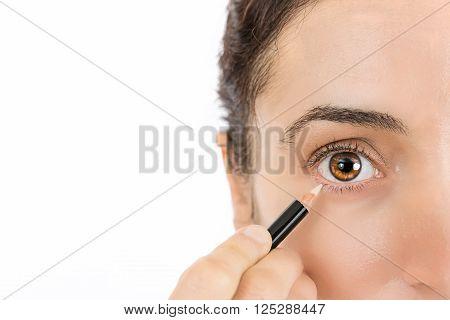 Woman eye close up using eye liner. Isolated on white background.