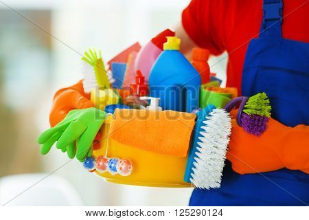 Young janitor holding cleaning products and tools on tub, close up