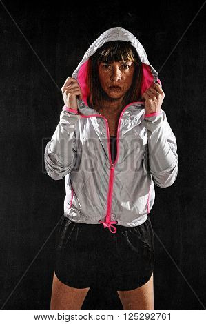 40s fit and strong sport freckles woman wearing training jacket hood on posing defiant in cool attitude in gym club harsh light advertising style isolated on black background in fitness concept poster