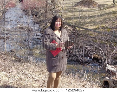 Professional looking mid aged Filipina standing beside a fast moving drainage ditch.