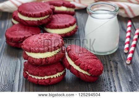 Red velvet sandwich cookies with milk on a wooden table
