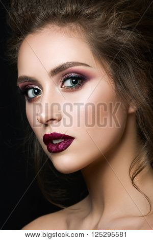 Portrait of young beautiful woman with evening make up over black background. Multicolored smokey eyes and dark red velvet mat lips. Luxury skincare and modern fashion makeup concept. Studio shot.