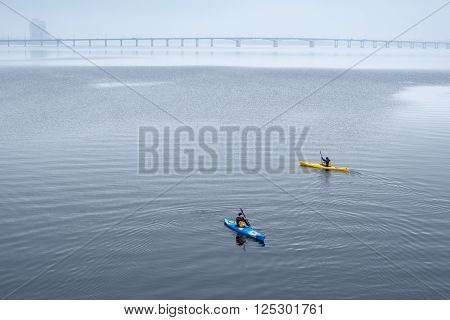 two men rowing a kayak along the river in the city cold and rainy weather