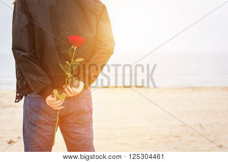 Man with a rose behind his back waiting for love. Date on the beach. Romantic surprise