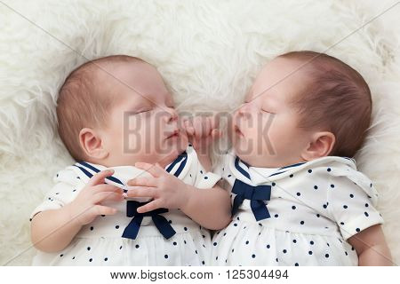 Newborn twins sisters sleeping on white fur, wearing sailor dresses. Maritime