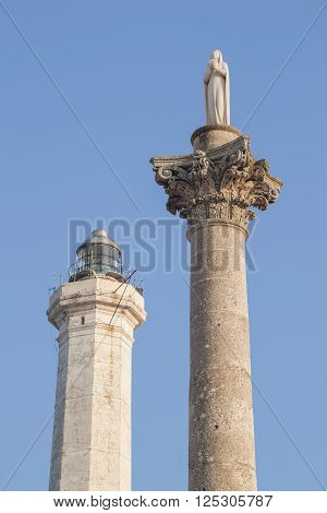 The lighthouse of Santa Maria di Leuca Italy near the high tower crowned by the statue of Saint Mary