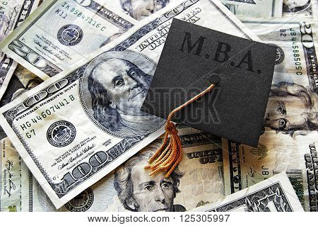 MBA graduation cap on hundred dollar bills -- Masters of Business Administration concept