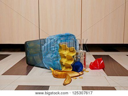 Full inverted garbage basket on kitchen floor