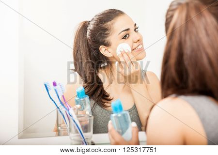 Happy young Hispanic brunette using makeup remover with a cotton pad in the bathroom poster