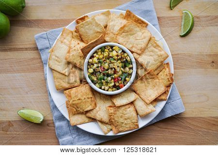 Corn Salsa with Pita Chips on Wood Background.